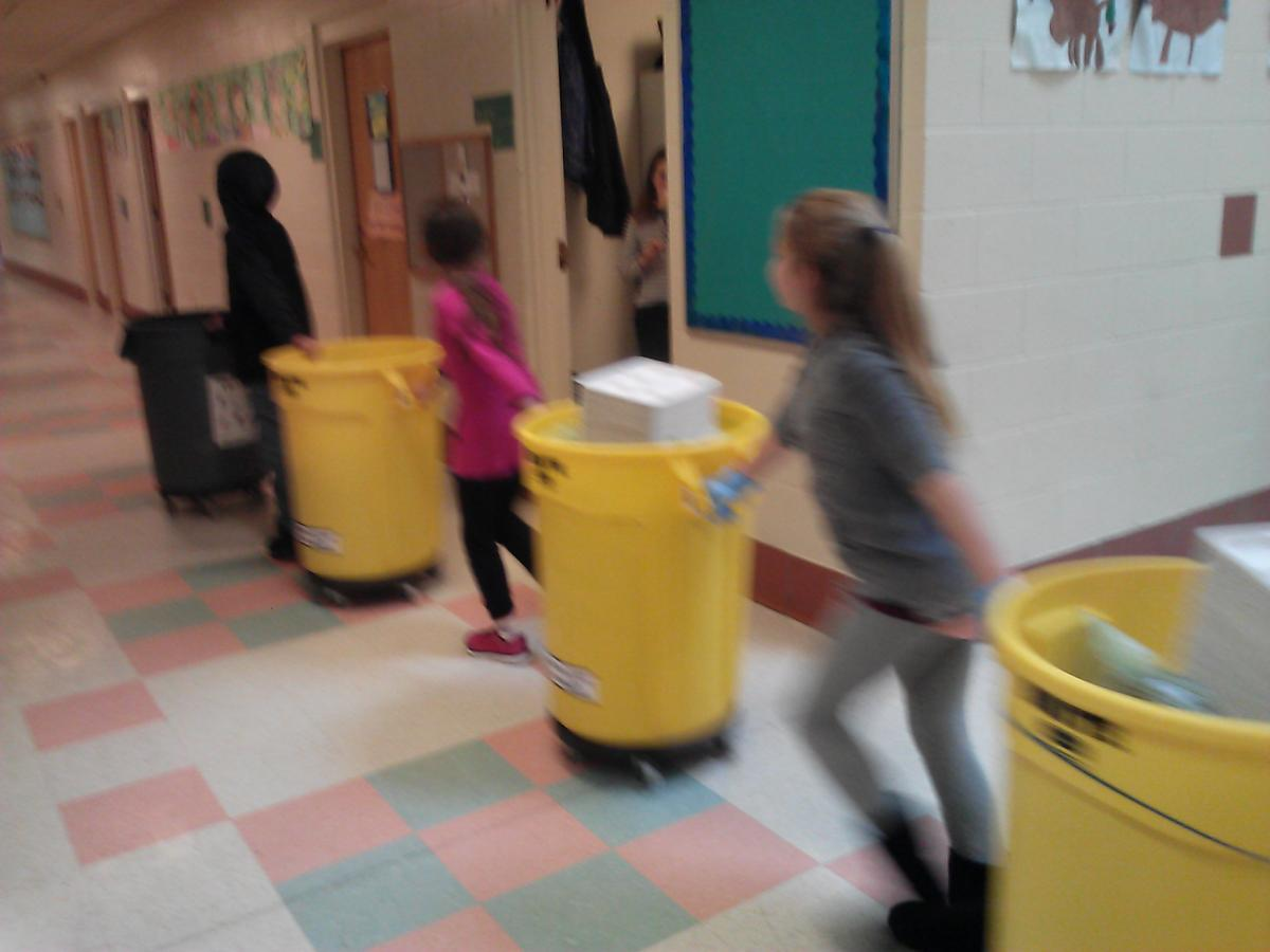 Students pushing barrels of compost