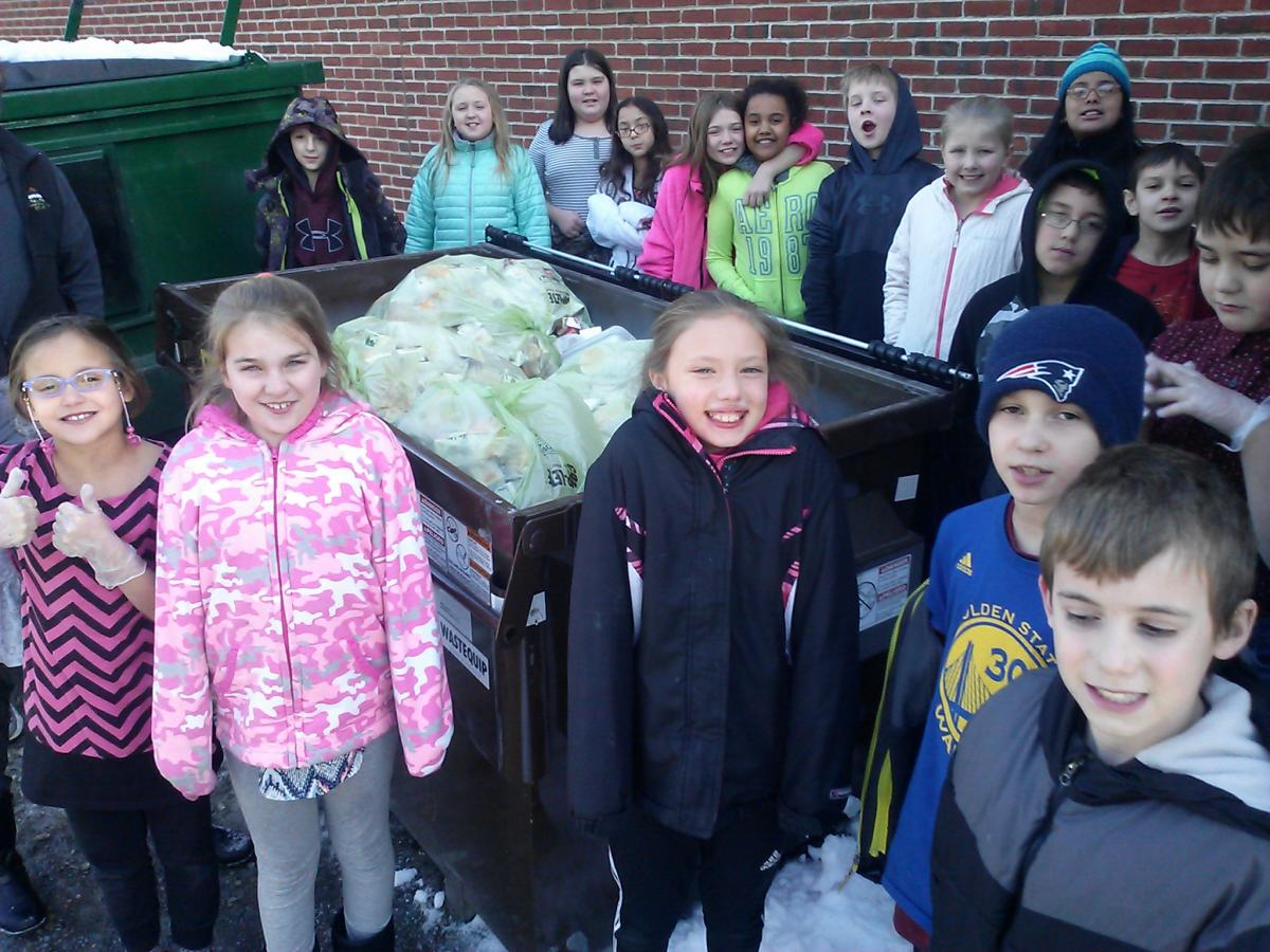 Students standing next to compost