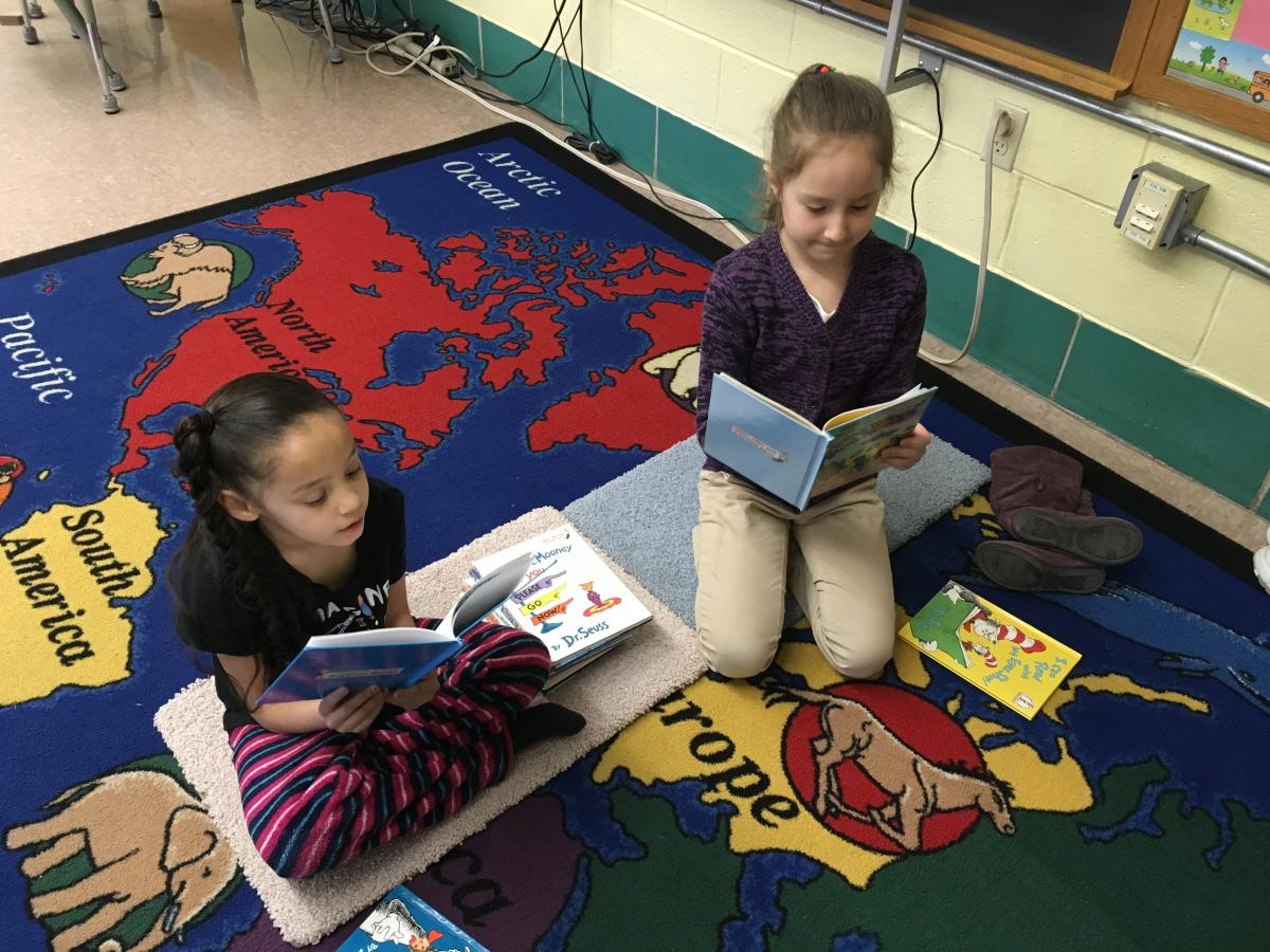2 Newton students reading on a rug