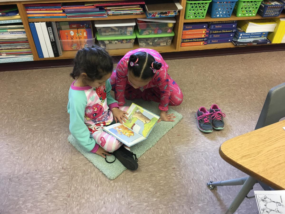 2 newton students reading on a rug 2