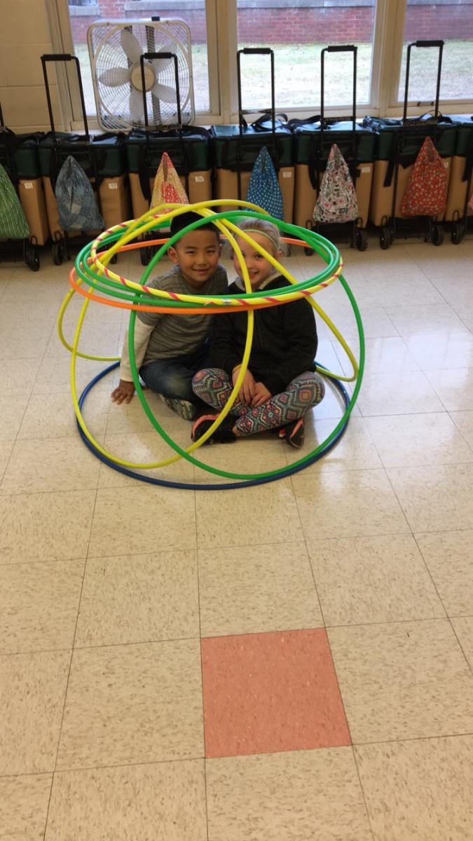 2 Newton students playing with hoola hoops